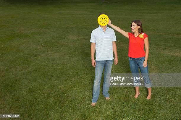 Girl holding flying disk over boy's face