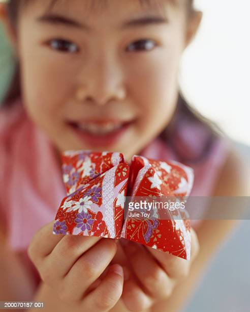 Girl (8-10) holding folded  origami paper  fortune toy, portrait