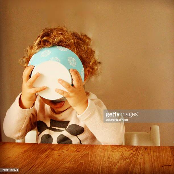 Girl (2-3) holding food bowl to her face