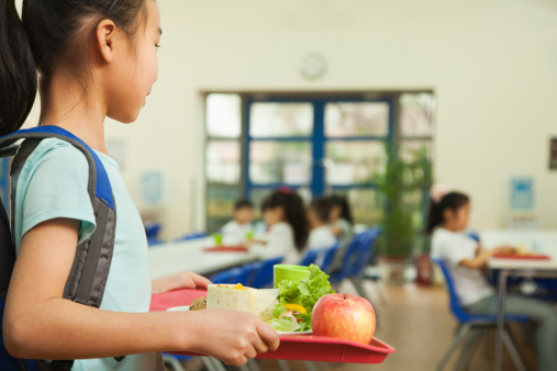 Girl holding food tray in school cafeteria 455188015