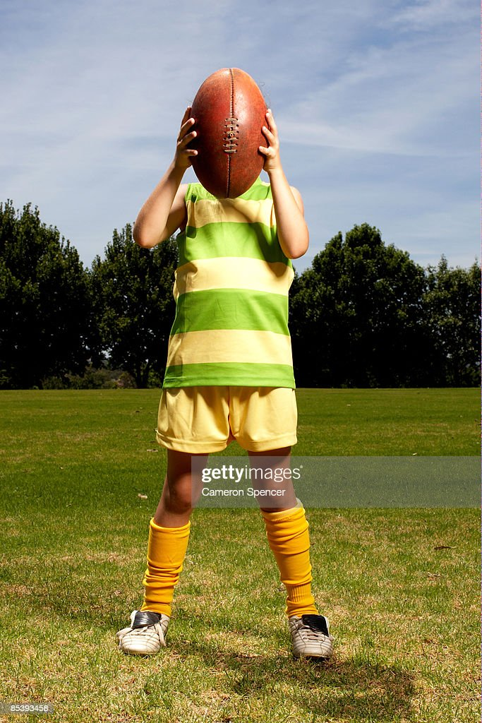 Girl holding football in front of her face : Stock Photo