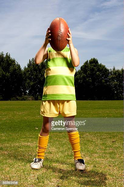 girl holding football in front of her face - cameron young - fotografias e filmes do acervo