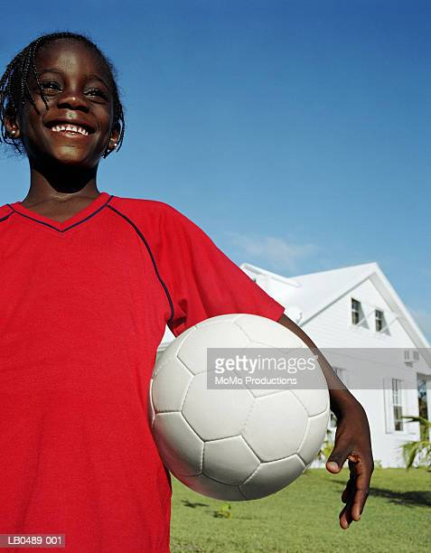 Girl (7-9) holding football in front of house, close-up