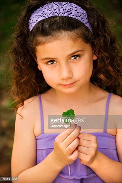 girl holding four-leaf clover - 4 leaf clover stock-fotos und bilder
