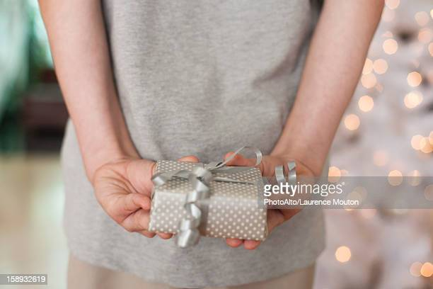 Girl holding gift behind back