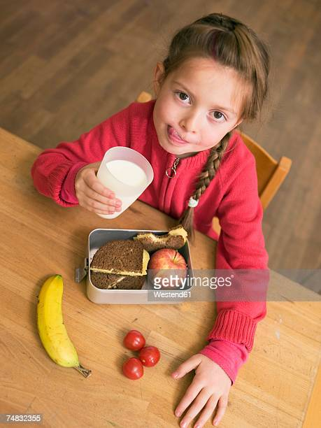 Girl (4-7) holding glass of milk and lunch box by desk, elevated view