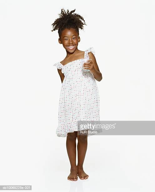 Girl (6-7) holding glass of milk, smiling, portrait
