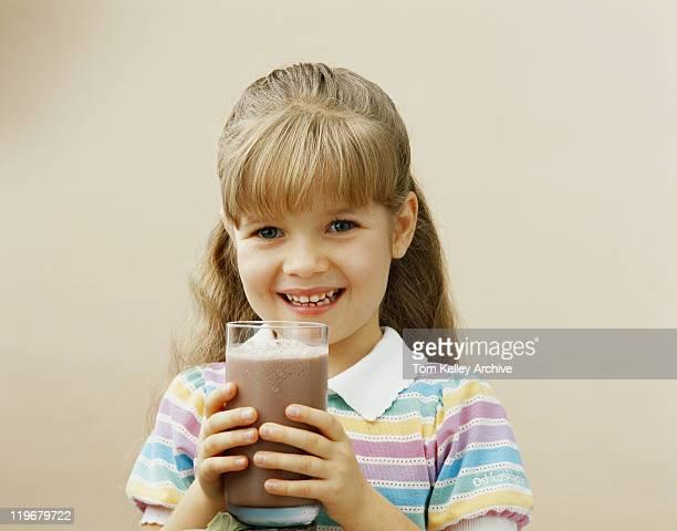 Girl holding glass of milkshake, smiling, portrait