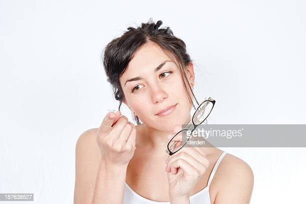 Girl holding glasses in one hand and contact lens other hand