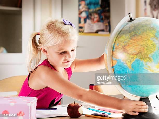 Girl holding globe at desk