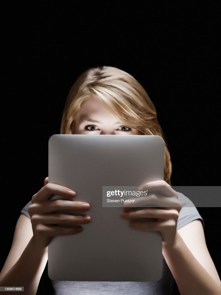 Girl holding glowing digital tablet : Stock Photo