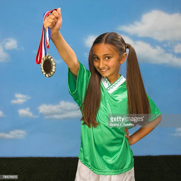 Girl holding gold medal