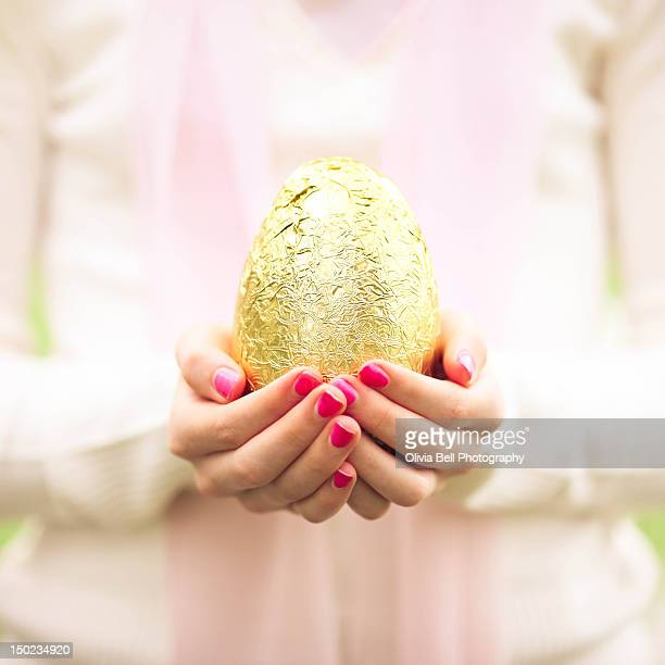 girl holding golden easter egg in hands - easter egg stock pictures, royalty-free photos & images