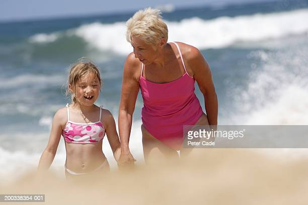 Girl (7-9) holding grandmother's hand on beach, smiling