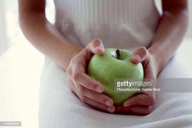 Girl holding green apple, mid section