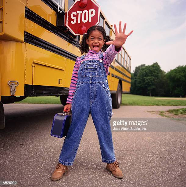 Girl (8-10) holding hand out in front of schoolbus