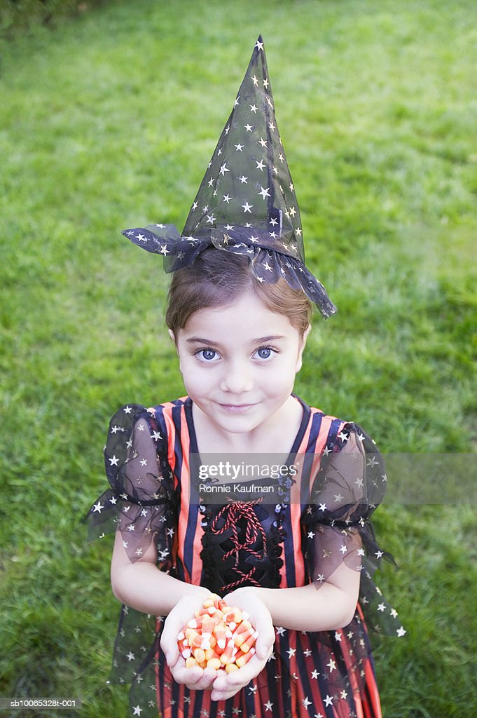 Girl (4-5) holding handful of candy corn, elevated view : Foto stock