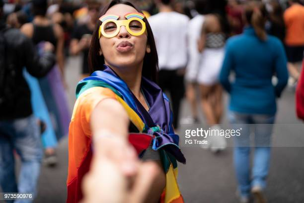 girl holding hands and following boyfriend on street party - pride stock pictures, royalty-free photos & images