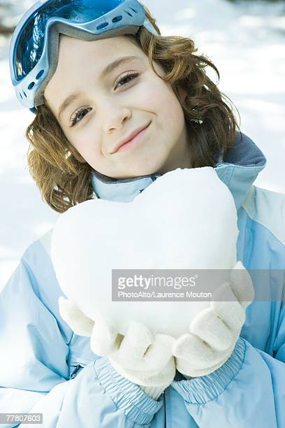 Girl holding heart made of snow, smiling at camera, portrait