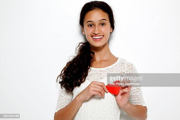 Girl holding heart to chest smiling at camera