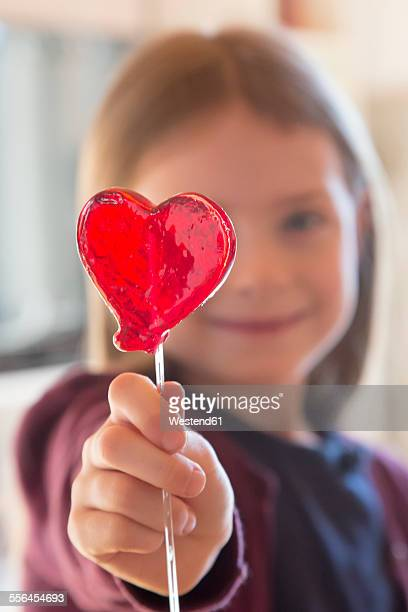 Girl holding heart-shaped lollipop