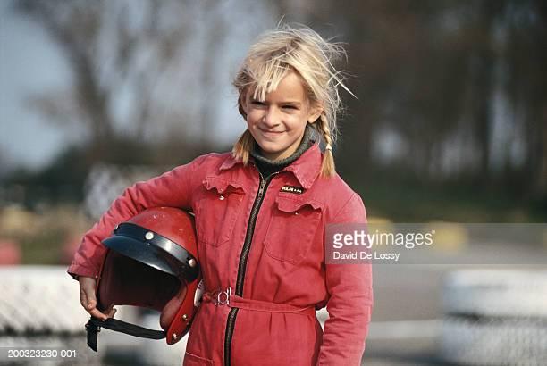 Girl (6-7) holding helmet, smiling