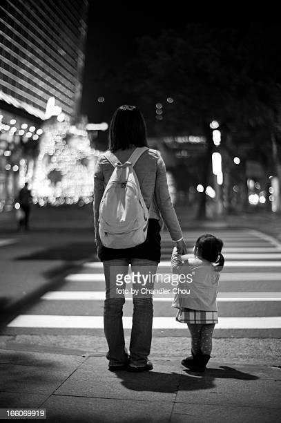 girl holding her mom's hand cross road