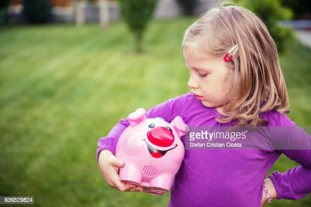 Girl holding her piggy bank