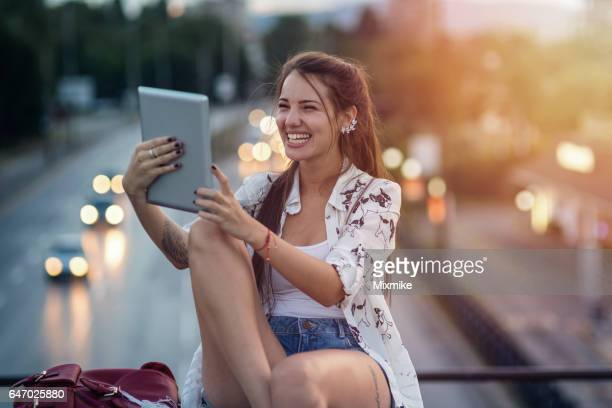 Girl holding her tablet and laughing