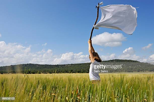 Girl holding high a white flag in wheat field