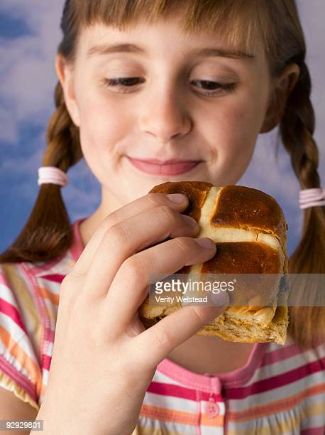 Girl holding hot cross bun