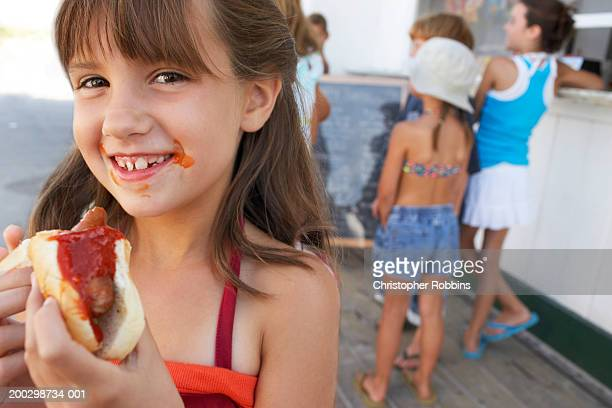 Girl (8-10) holding hotdog, sauce around mouth, smiling, portrait