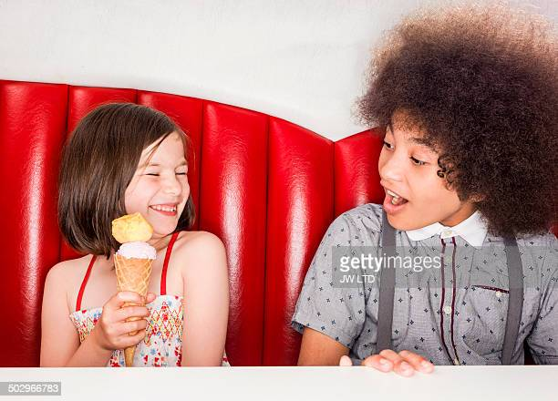 Girl holding ice cream, boy looking enviously