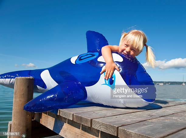 Girl holding inflatable whale on dock