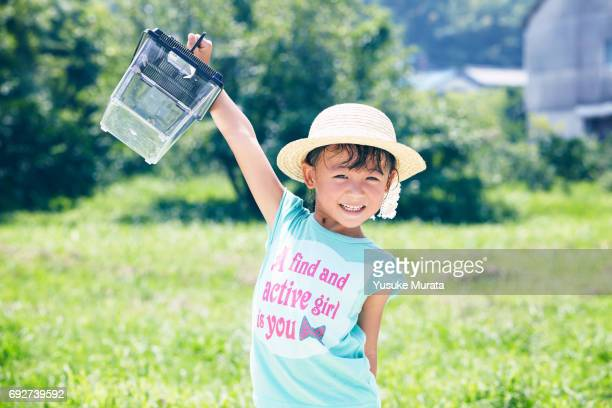 Girl holding insect cage