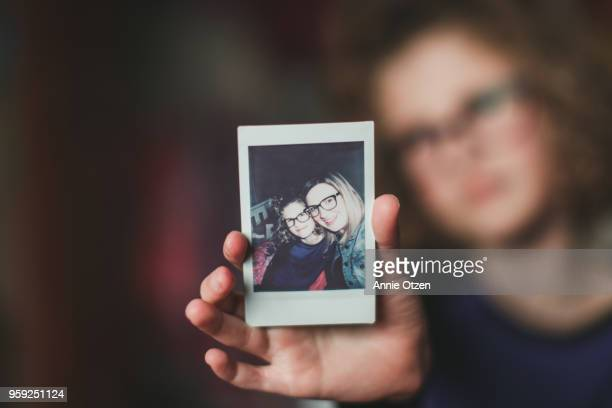 girl holding instant film photo - photography themes stock pictures, royalty-free photos & images
