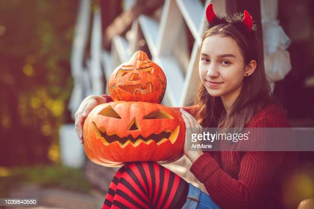 girl holding jack o' lantern and painted pumpkin - devil costume stock photos and pictures