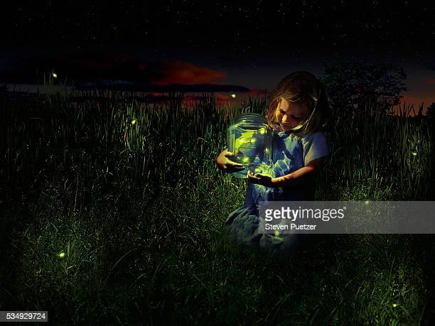 girl holding jar of fireflies - グローワーム ストックフォトと画像