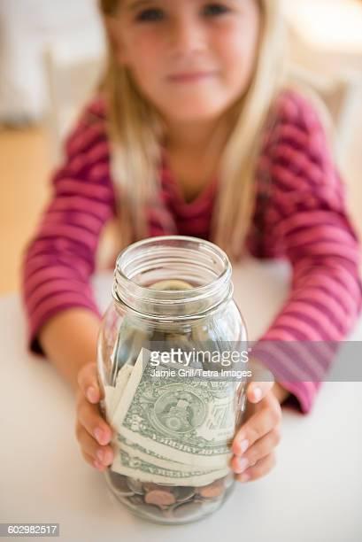 Girl (6-7) holding jar with savings