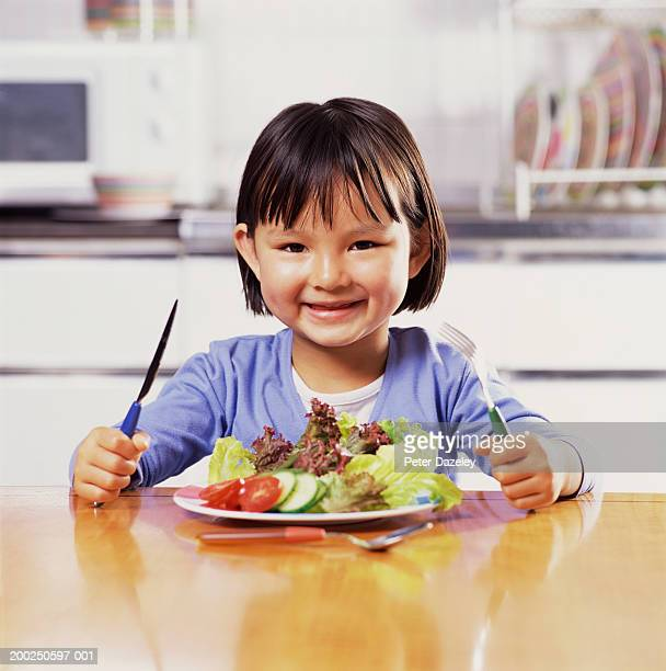 Girl (3-5) holding knife and fork, salad on table, smiling, portrait