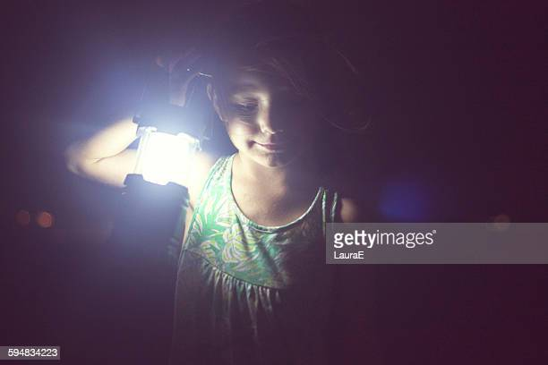 Girl holding lamp in the darkness
