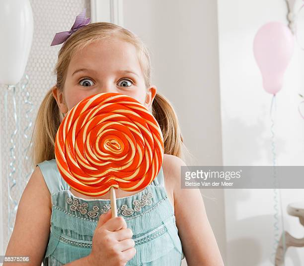 Girl holding large lollipop.