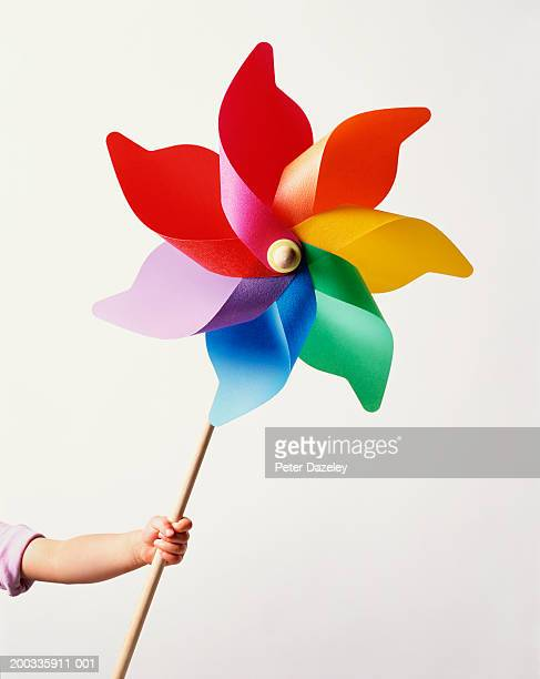 Girl (2-4) holding large paper windmill (digital composite)