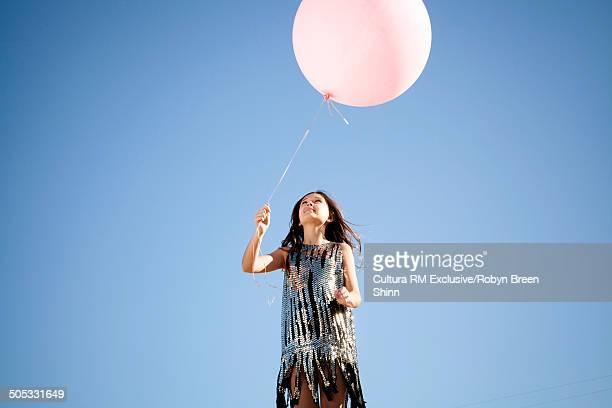 Girl holding large pink balloon