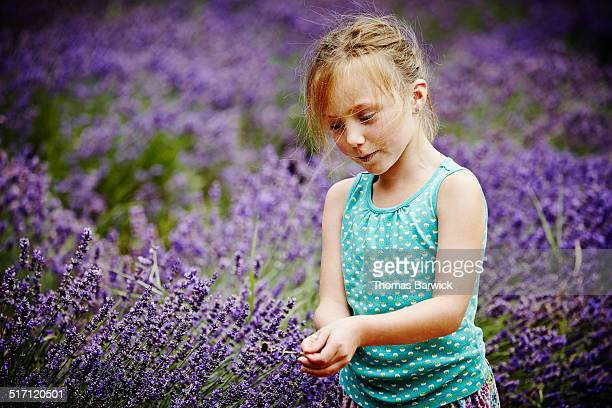 Girl holding lavender stem with bumble bee