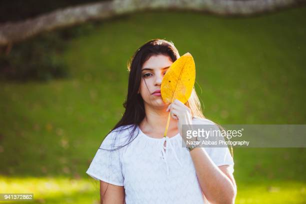 Girl holding leaf and covering part of her face with it.