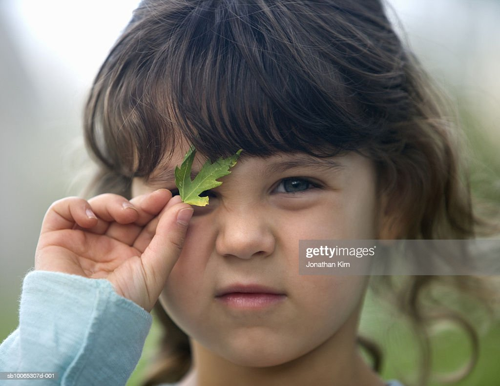Girl (4-5) holding leaf over eye, close-up : Foto stock
