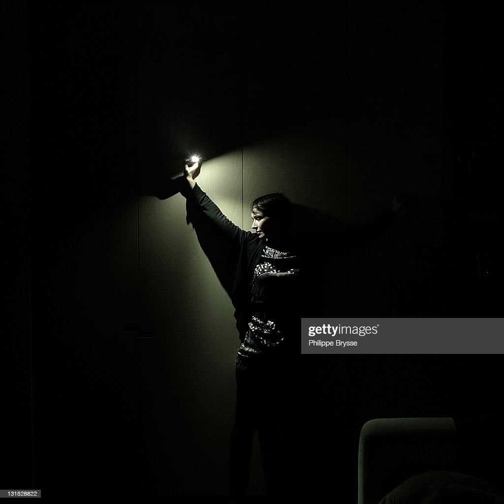 Girl holding light in dark room : Stock Photo