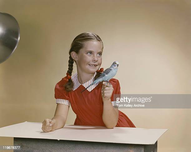 Girl holding lovebird on finger and looking away