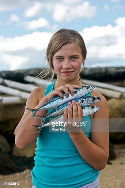 Girl holding Mackerel fish that she caught
